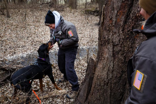 Marsha Patterson rewards Tammy Hansen's dog, Bailey, after she found Patterson hiding in a tree during a trailing drill at Heritage Park on Wednesday, Nov. 28, 2018, in Ankeny. Hansen and Patterson are part of a group of women who assist authorities across the country in tracking missing persons.