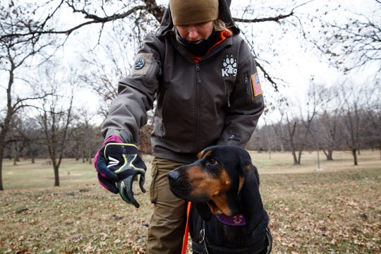 Tammy Hansen gives her dog, Bailey, a glove as a scent article for a trailing drill at Heritage Park on Wednesday, Nov. 28, 2018, in Ankeny.