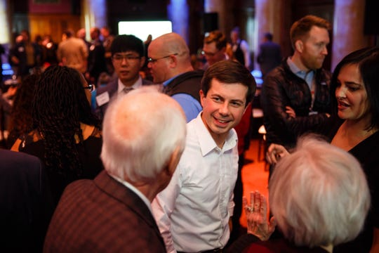 Mayor Pete Buttigieg of South Bend, Indiana, talks to Dr. Dow Bates during Progress Iowa's Holiday Party on Thursday, Dec. 20, 2018, in Des Moines.