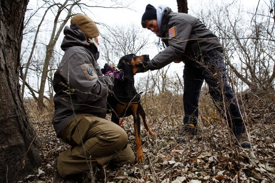 Marsha Patterson, right, rewards Tammy Hansen's dog, Bailey, after Bailey found Patterson hiding in a tree during a trailing drill at Heritage Park on Wednesday, Nov. 28, 2018, in Ankeny.