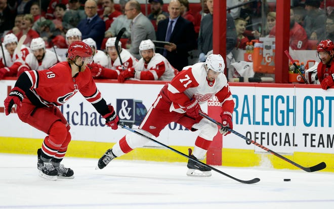 Carolina Hurricanes' Dougie Hamilton (19) and Detroit Red Wings' Dylan Larkin (71) chase the puck during the first period of an NHL hockey game in Raleigh, N.C., on Thursday, Dec. 20, 2018.