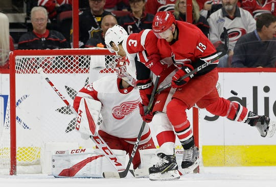 Detroit Red Wings' Nick Jensen (3) and goalie Jonathan Bernier defend the net in front of Carolina Hurricanes' Warren Foegele (13) during the first period of an NHL hockey game in Raleigh, N.C., on Thursday, Dec. 20, 2018.