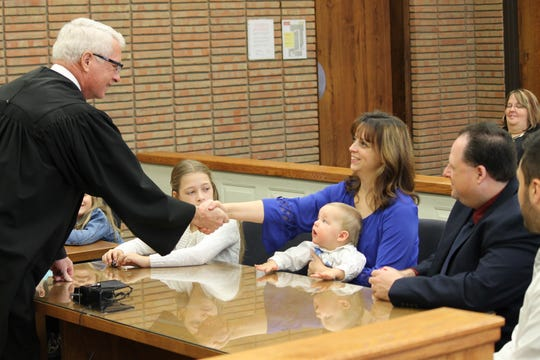 Nikki Stromberg shakes hands with Judge Elwood Brown during adoption proceedings in Port Huron as her husband, Reid, watches. She holds her foster son, David, as his new big sister Beth watches proceedings on Jan. 15, 2016.