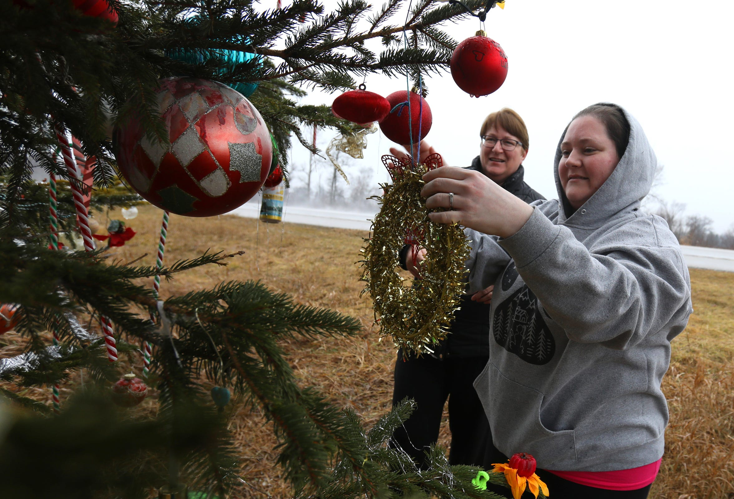 Laura Bigger of Twin Lakes, left, and her daughter Michelle Walters pulled over along I-75 on Dec. 20, 2018 to add plastic candy canes and a gold wreath to a Christmas tree in Moffatt Township.