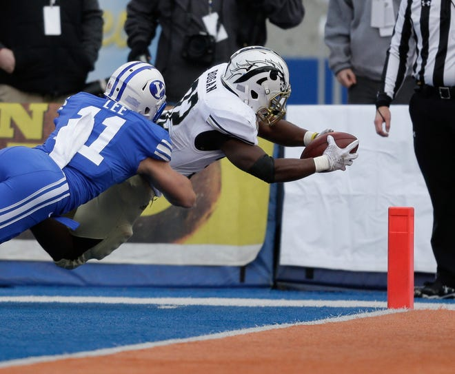 Western Michigan running back Jamauri Bogan dives into the end zone as BYU defensive back Austin Lee attempts the tackle in the first half of the Famous Idaho Potato Bowl, an NCAA college football game, Friday, Dec. 21, 2018, in Boise, Idaho.