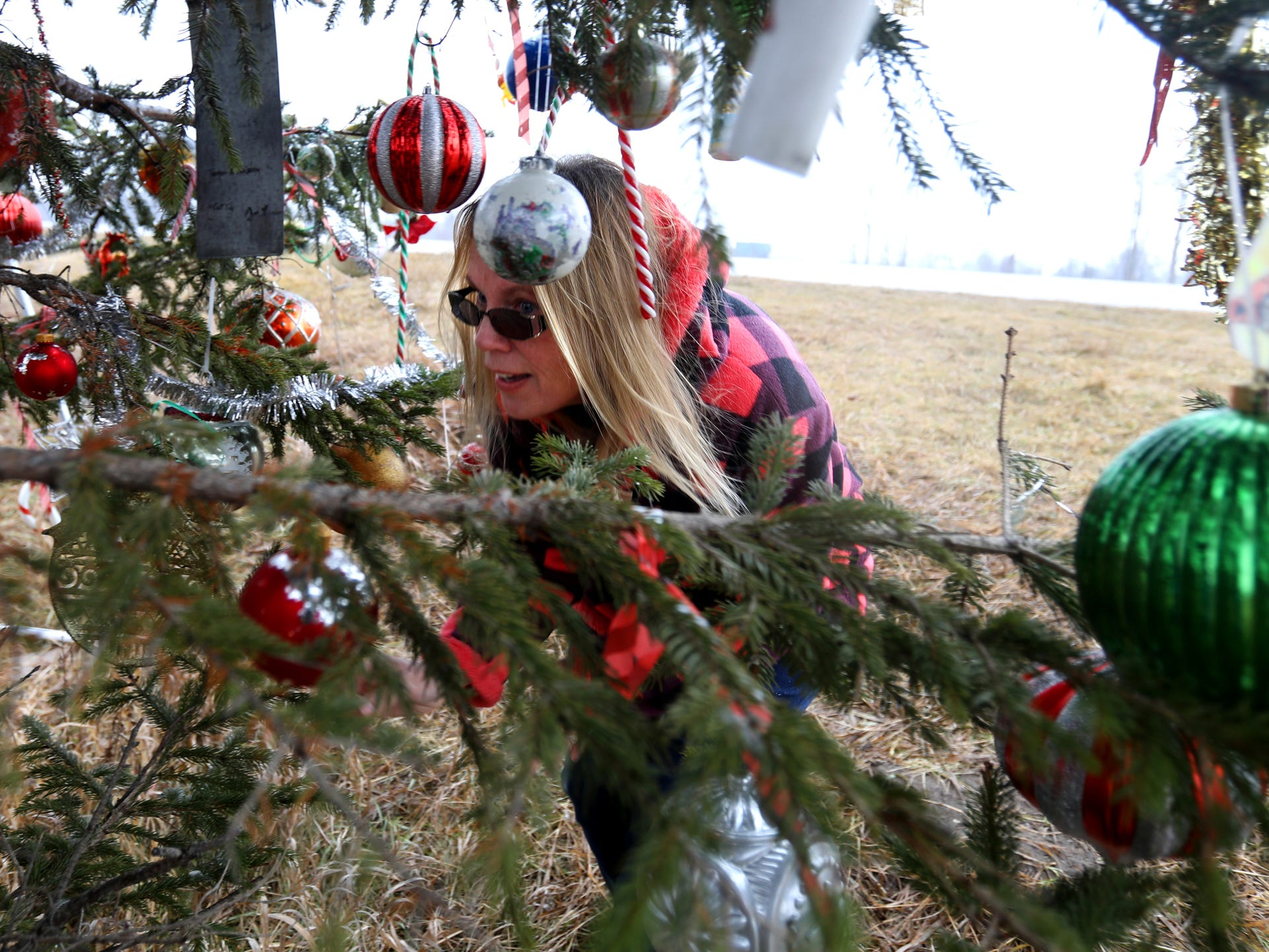 Kathy Porter looks at the newer Christmas ornaments that have been added to the tree that serves as a memorial for her son along I-75 in Moffatt Township, Michigan on Friday, Dec. 20, 2018.