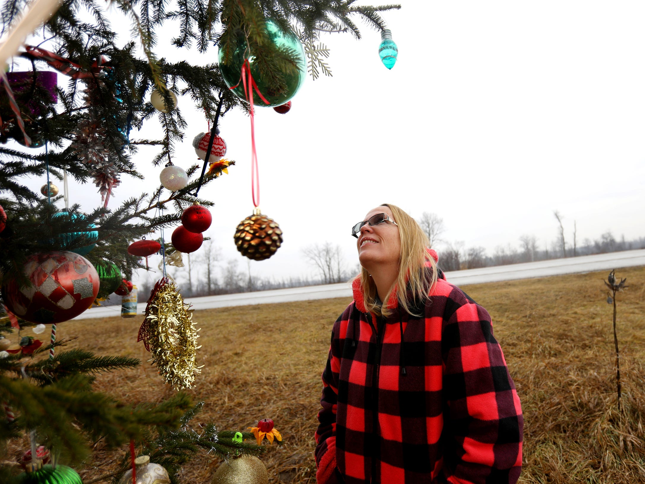 Kathy Porter looks at the new Christmas ornaments added to the pine tree planted at the site of her son Jason's death, who was killed by a drunk driver 20 years ago.