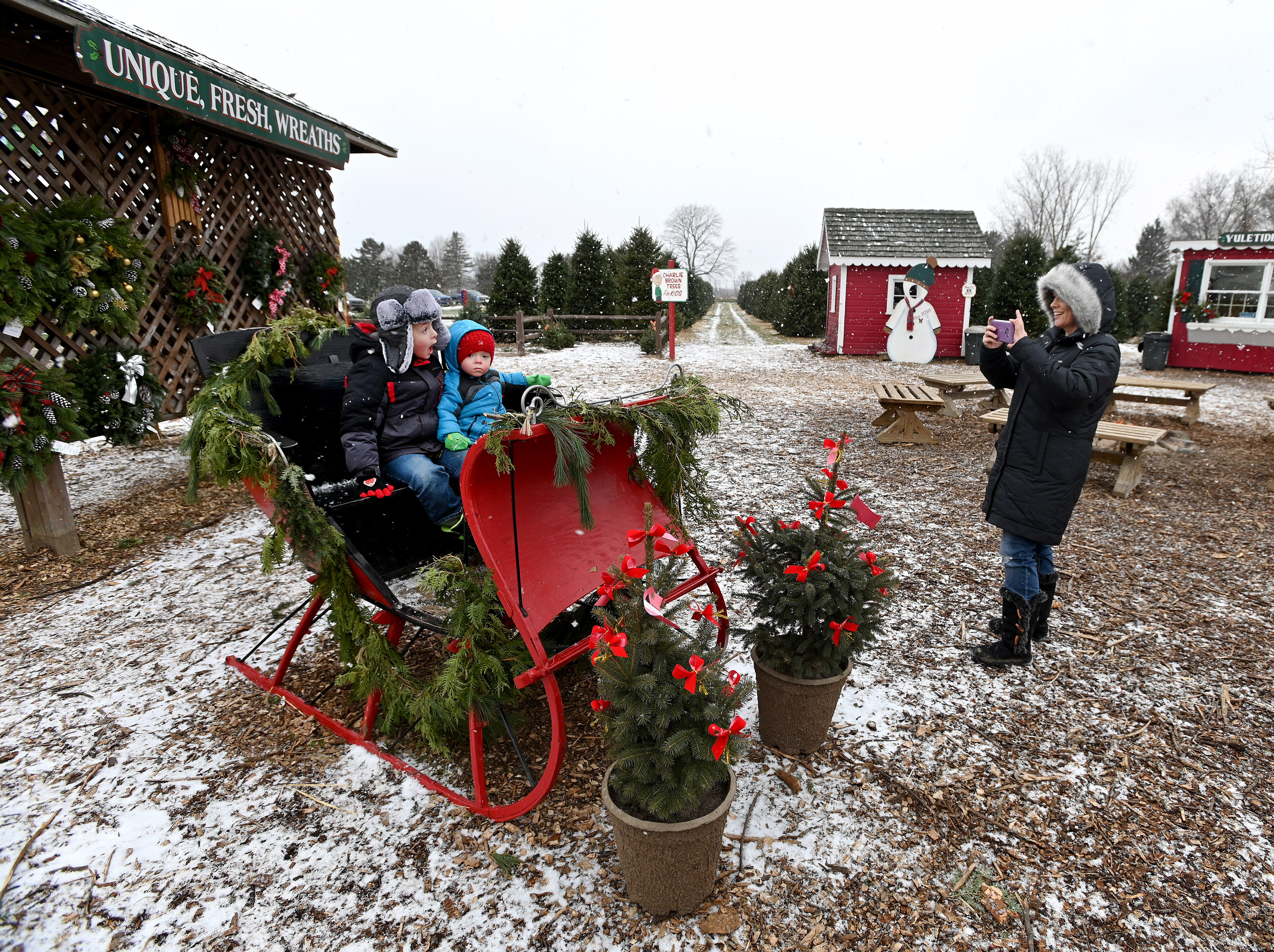 "Amber Druelle of St. Charles captures a memory of her kids, Bryce and Brooks, on a ""cutter"" sleigh at the Kluck family Christmas tree farm."