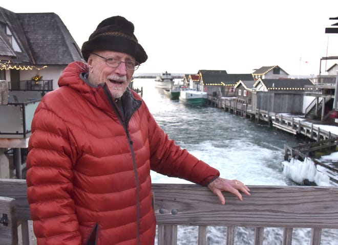 Keith Burnham stands on a bridge overlooking Leland's Fishtown, where he has been honored for his love of the iconic shanties and the commercial fishing center by dedicating the first-ever illumination of the site.