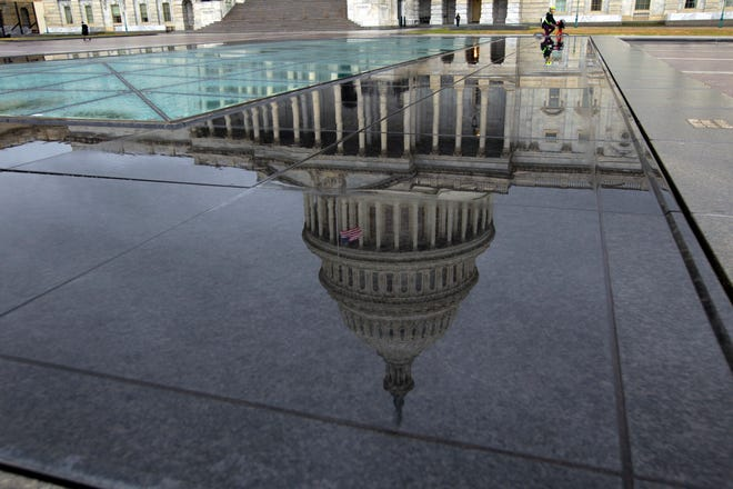 The U.S. Capitol is seen reflected after rain in Washington, Friday, Dec. 21, 2018.