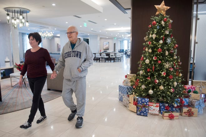 Michael Gerald and his wife, Leanne, walk through the lobby of the Homewood Suites Arlington while Michael is recovering from his 4th kidney transplant and waiting to get the medical clearance to return to Michigan.