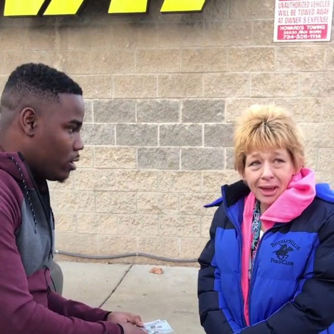 Detroit comedian HaHa Davis, left, gives money to an unnamed woman in need in this viral video which was shown Friday on the syndicated talk show 'The Real.'
