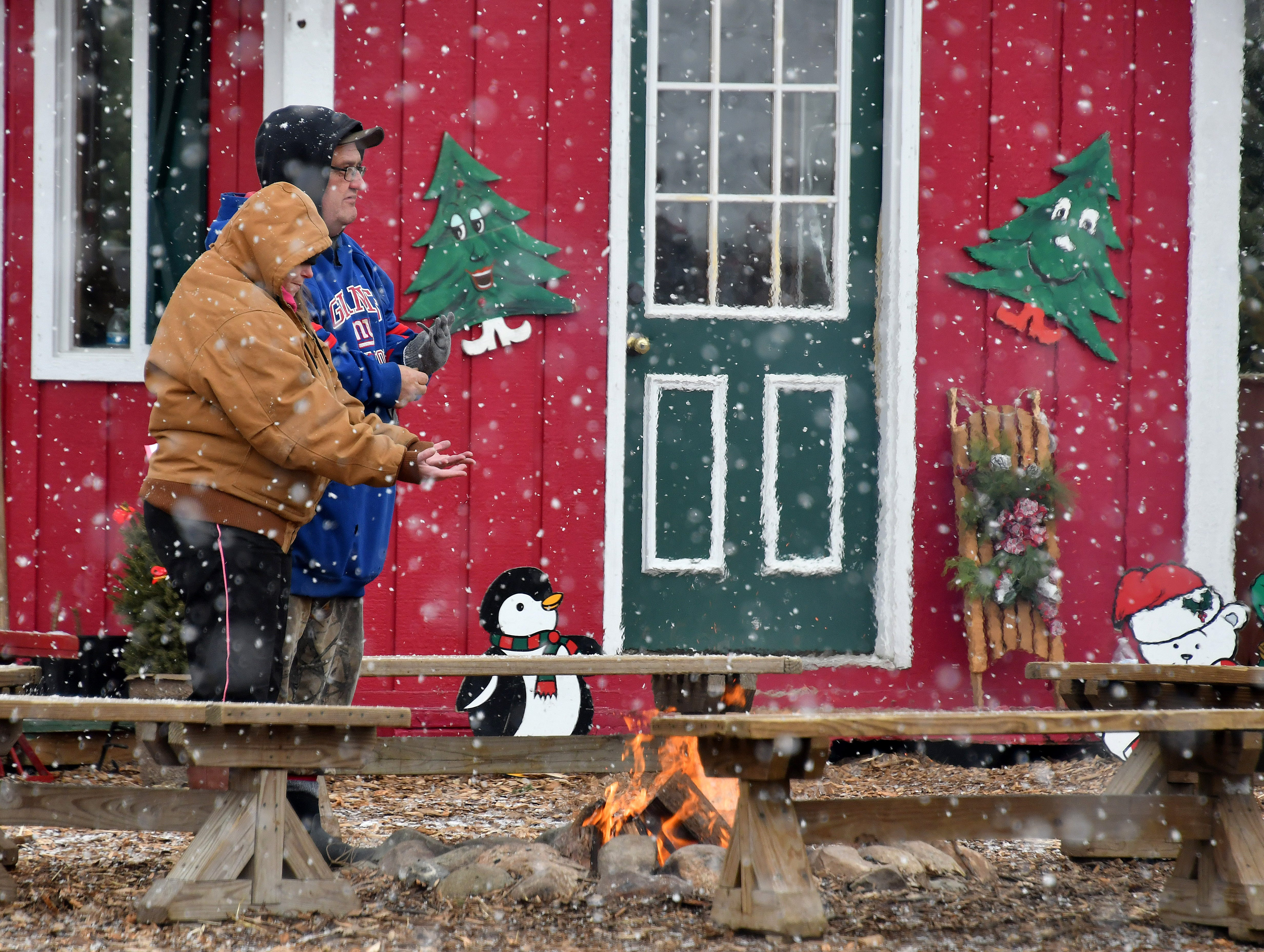 As the snow falls, a warming fire is kept burning for anyone who needs a little heat at the Kluck family Christmas Tree Village, while Christmas music plays from the building in the background.