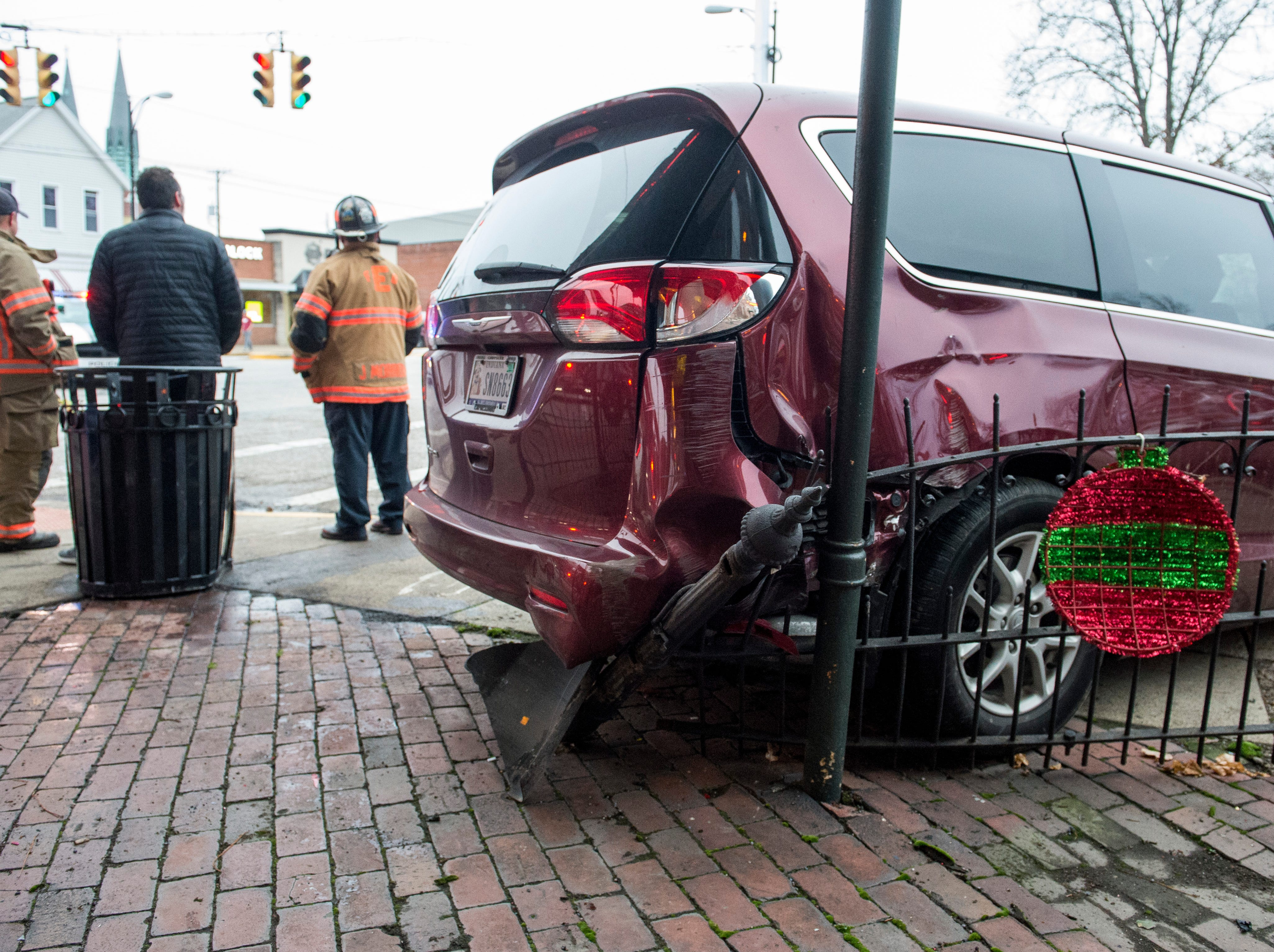 Evansville Police say a truck traveling west on Franklin Street lost a tire and veered onto the sidewalk in front of the library, colliding with an SUV trying to turn south on 10th Avenue. The SUV hit a parked minivan causing all three vehicles to hit the fence and awning of the Gerst Haus Friday, Dec. 21, 2018.