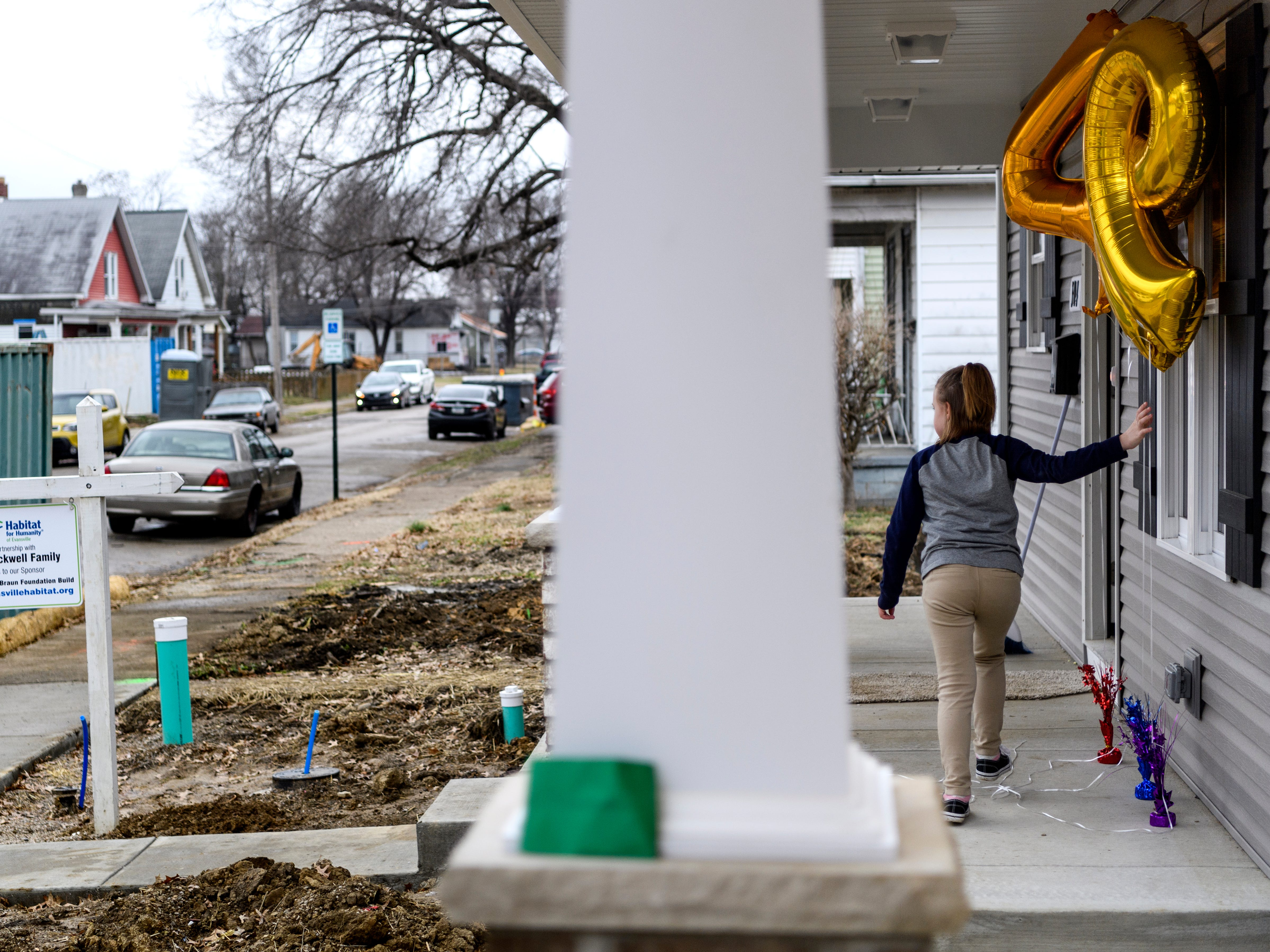 Bailie Douthitt, 10, plays with balloons displayed on her aunt Leslie Blackwell's porch before the 500th Habitat for Humanity home dedication ceremony on Bedford Avenue in Evansville, Ind., Thursday, Dec. 20, 2018. Blackwell's home was the 499th habitat home built in Evansville.