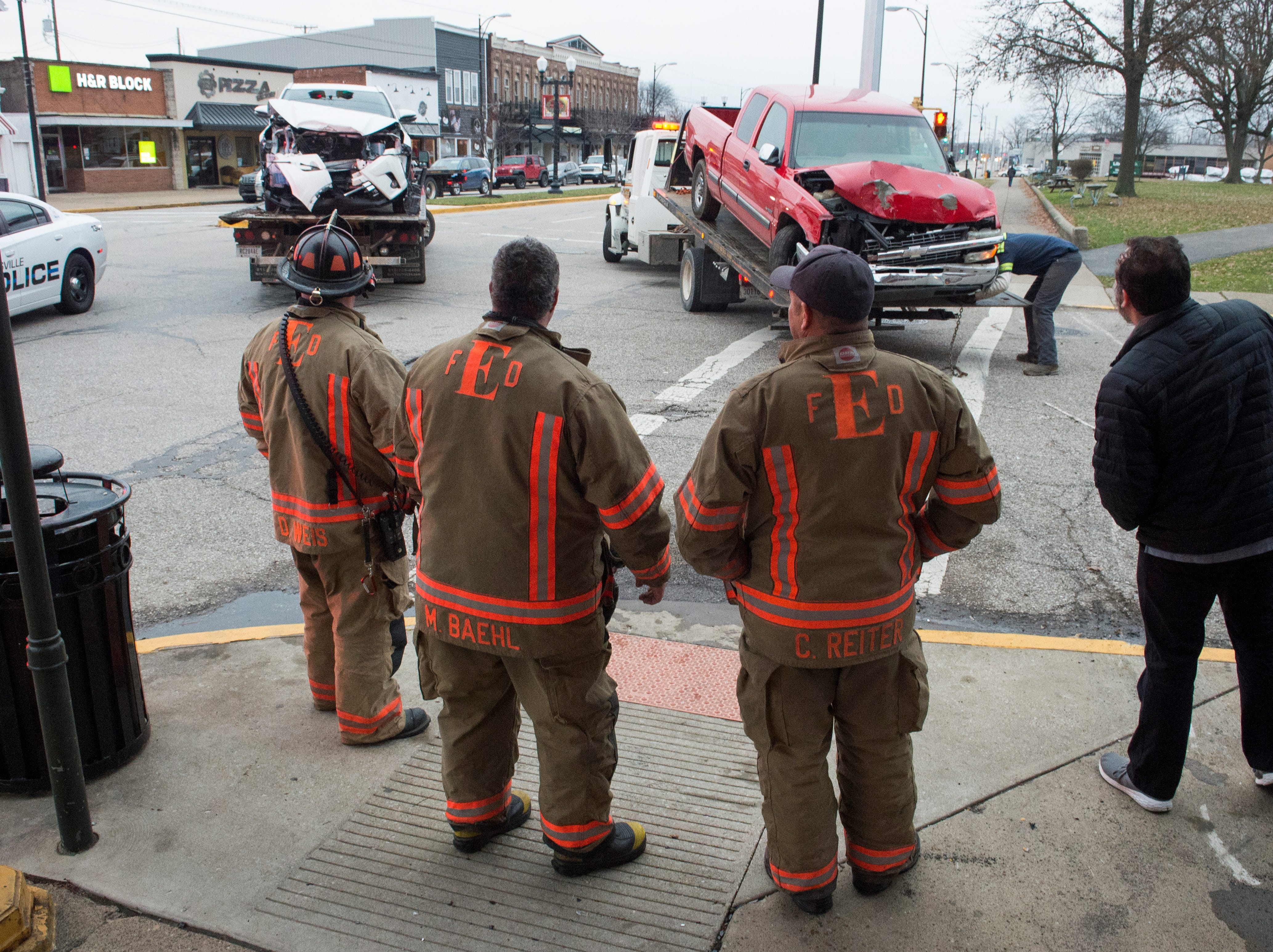 Member of the Evansville Fire Department Quint 5 squad looks at the damaged vehicles that were involved in a three-car crash on Franklin Street in front of the Gerst Haus Friday, Dec. 21, 2018.
