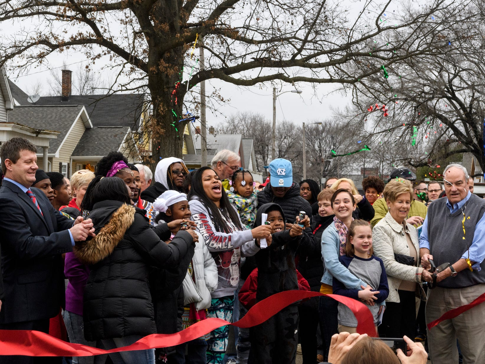 Four new homeowners and their family and friends participate in a ribbon cutting to celebrate the 500th Habitat for Humanity home dedication ceremony on Bedford Avenue in Evansville, Ind., Thursday, Dec. 20, 2018. Evansville's Habitat for Humanity is the 26th affiliate across the nation to reach 500 home builds in the community.