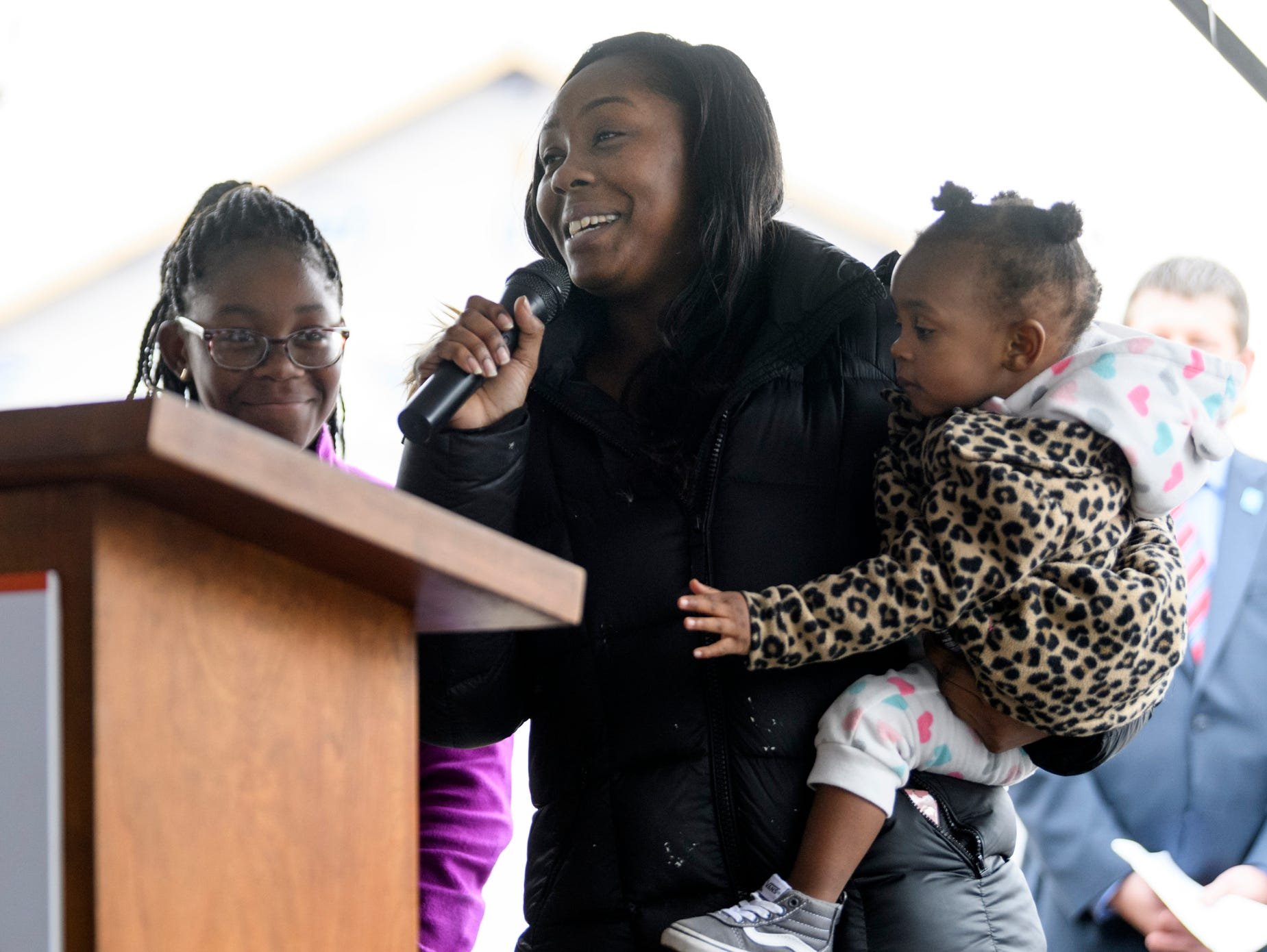 Tamisha Dilworth, the 500th homeowner, thanks the crowd for attending the Habitat for Humanity home dedication ceremony for four new homeowners, including her, as she is joined by two of her children Aliyah, left, and Teresa, right, at the podium on Bedford Avenue in Evansville, Ind., Thursday, Dec. 20, 2018.
