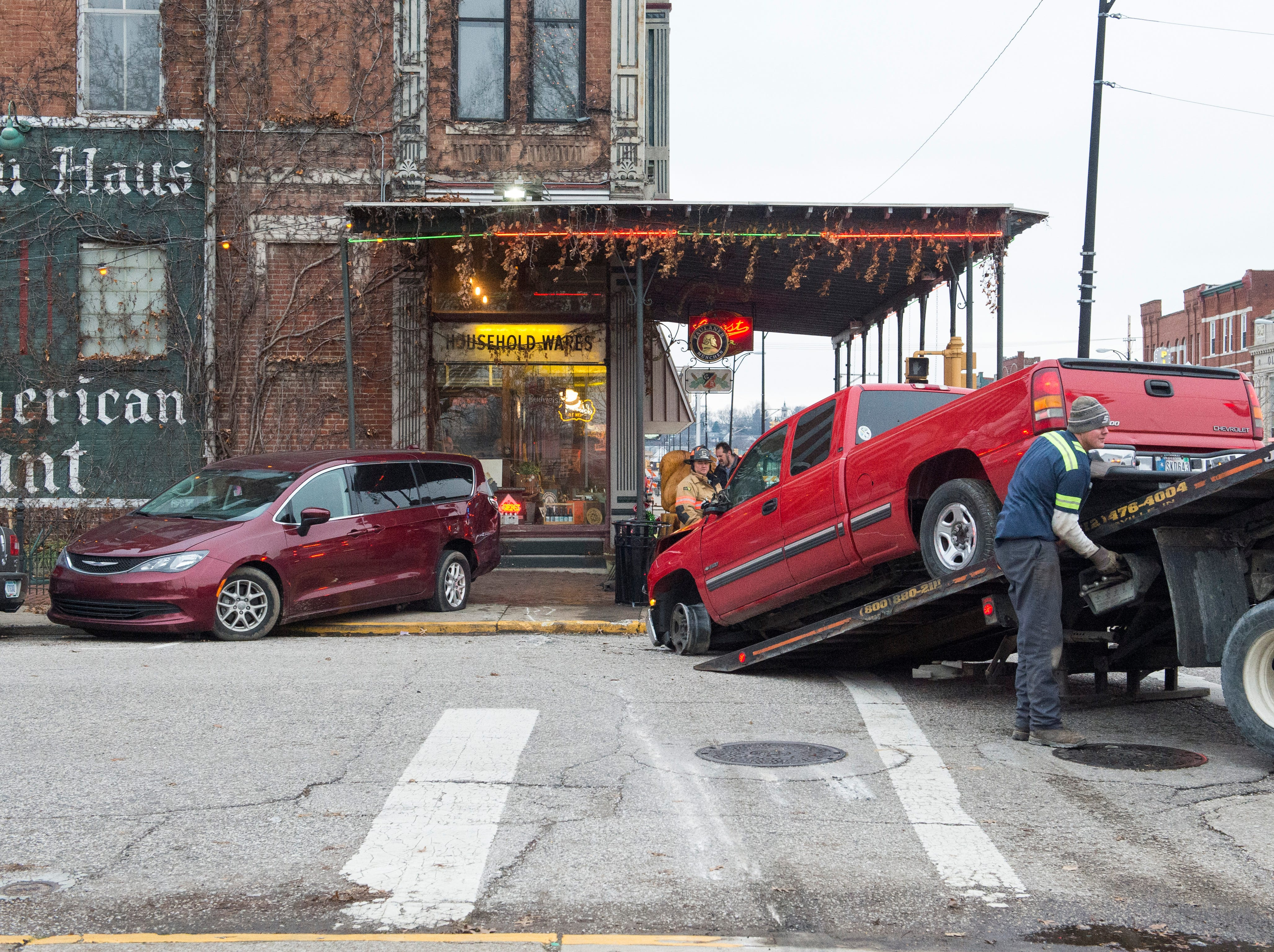 Evansville Police say a truck traveling west on Franklin Street lost a tire and veered onto the sidewalk in front of the library, colliding with an SUV trying to turn south on 10th Avenue. The SUV hit a parked minivan causing all three vehicles to hit the fence and awning of the Gerst Haus.