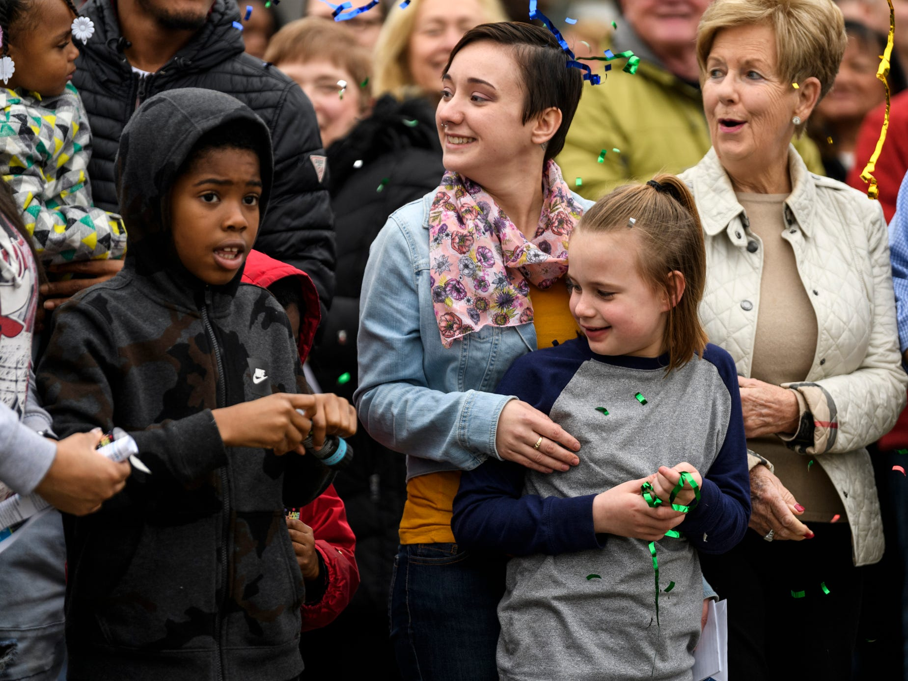 Leslie Blackwell, top center, and her niece Bailie Douthitt, 10, bottom center, react to confetti poppers busting around them during the 500th Habitat for Humanity home dedication ceremony on Bedford Avenue in Evansville, Ind., Thursday, Dec. 20, 2018.