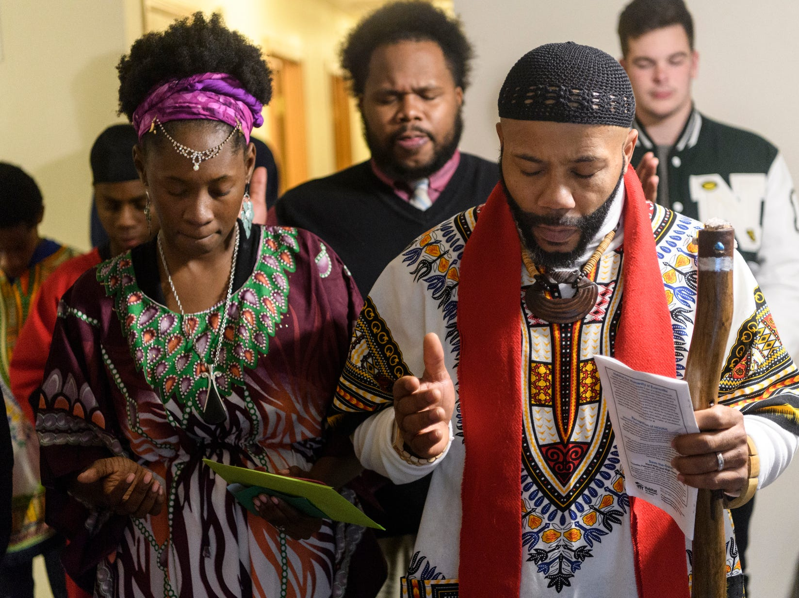 Homeowners MeShia, left, and Steven Kince, right, pray with their friends and family during a Hebrew home blessing provided by Pastor Yoshiyah, also known as Edward Logan, of Madisonville, Ky., following the 500th Habitat for Humanity home dedication ceremony on Bedford Avenue in Evansville, Ind., Thursday, Dec. 20, 2018. The Kinces and five of their children are expected to move into their five bedroom, two bathroom house at the end of January.