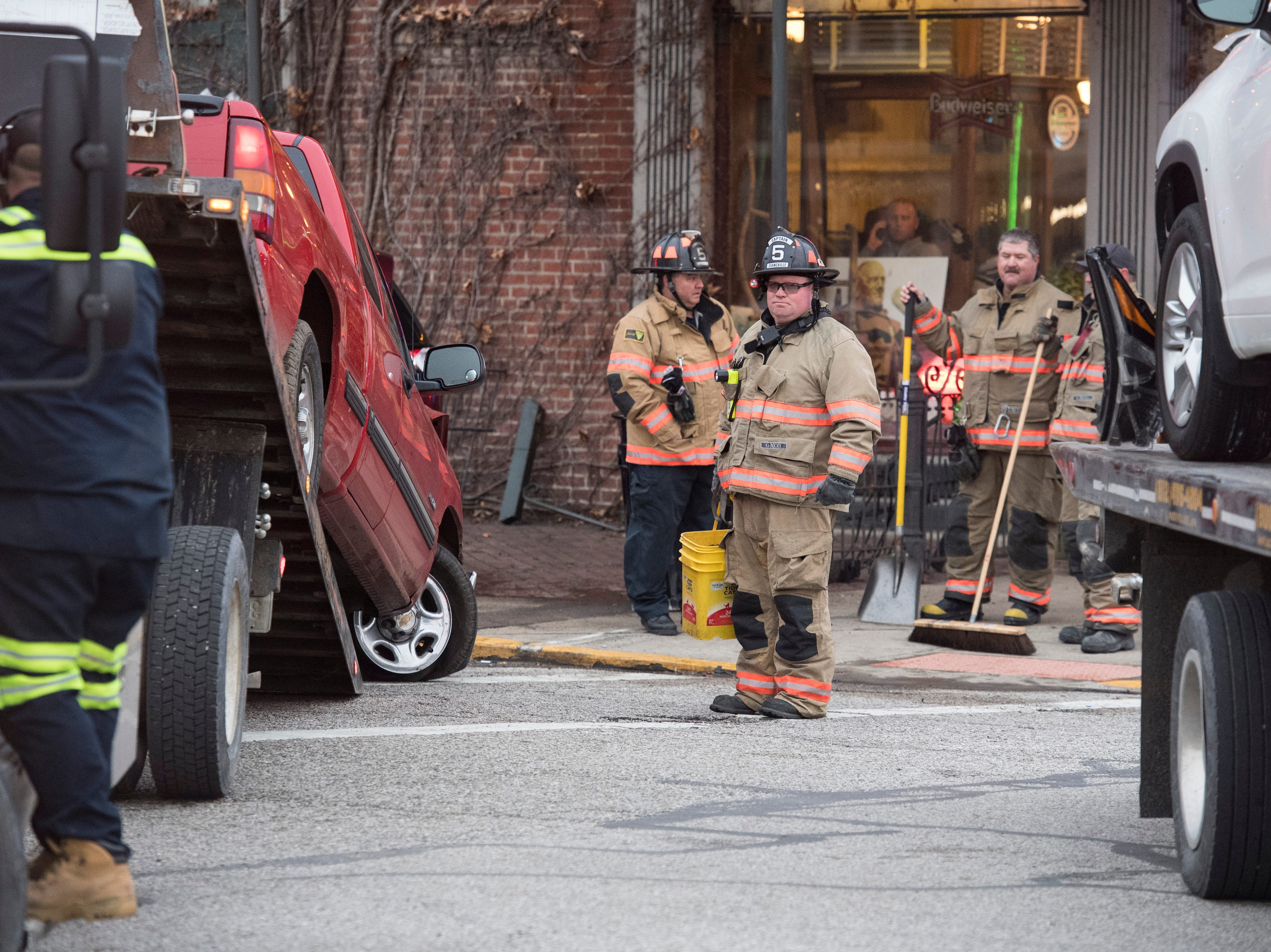 EFD Quint 5 Captain Dave Weis watches as a truck that caused a three-car crash in front of the Gerst Haus on Franklin Street is pulled onto a flatbed truck Friday, Dec. 21, 2018.