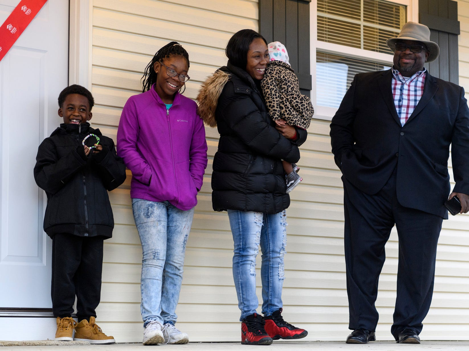 Tamisha Dilworth, second from right to left, and her three children, Teresa, Aliyah and Travon receive a home blessing from The Rev. Larry Roscoe, right, Pastor of Nazarene Missionary Baptist church, during the 500th Habitat for Humanity home dedication ceremony on Bedford Avenue in Evansville, Ind., Thursday, Dec. 20, 2018. Dilworth is Evansville's 500th Habitat for Humanity homeowner.