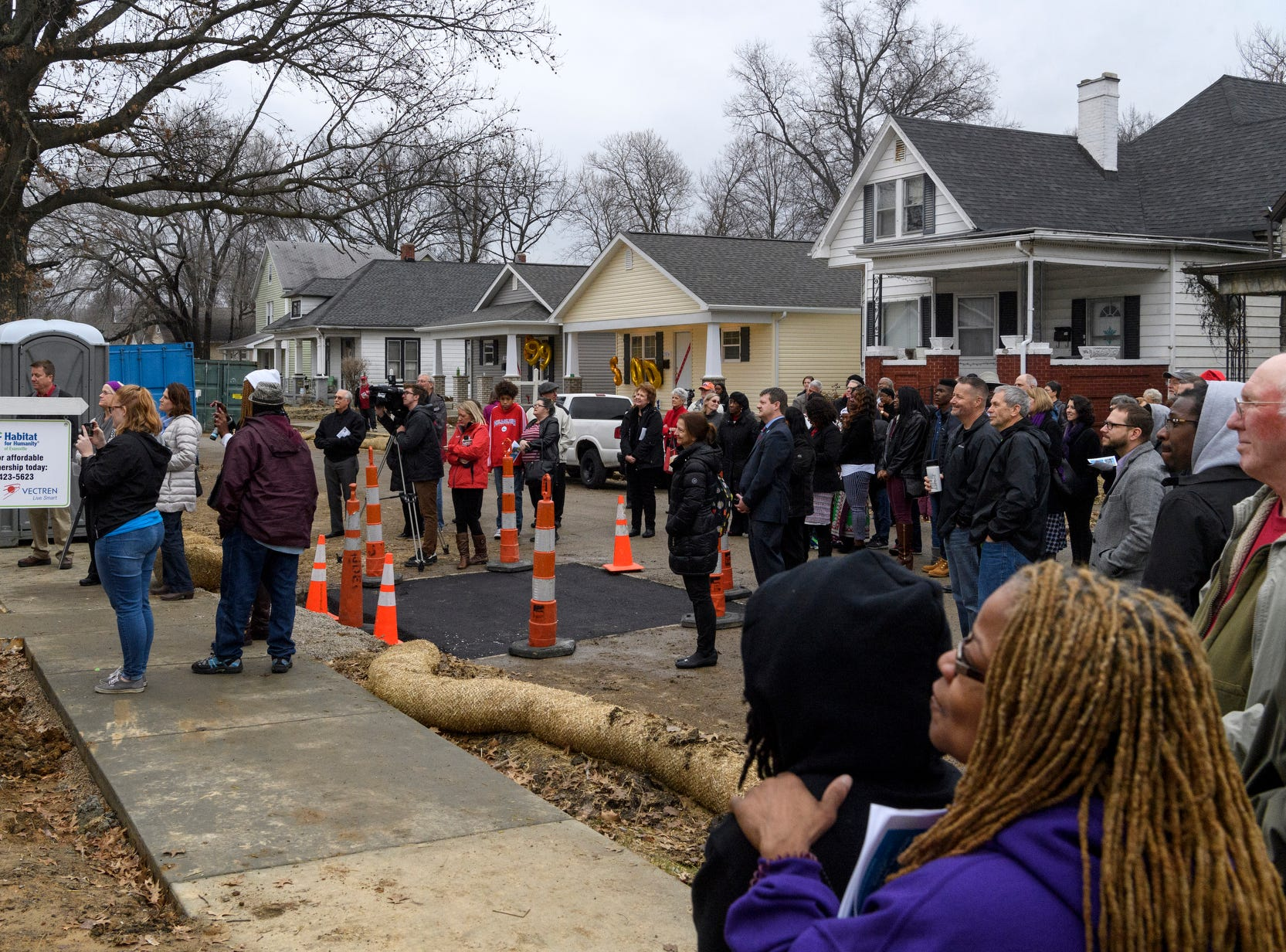 Community members gather on Bedford Avenue to watch Tiffany Wilson, not pictured, receive the keys to her new home during the 500th home dedication ceremony for her and three of her new neighbors in Evansville, Ind., Thursday, Dec. 20, 2018. Evansville's Habitat for Humanity is the 26th affiliate nationwide to reach 500 home builds.