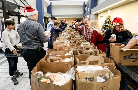 Fond du Lac Police officers, Festival Foods representatives and other volunteers help to bag 70 Christmas dinners Friday, Dec. 21 at the Fond du Lac Police Department, to be added to toys that will be delivered to 70 families as part of the Fond du Lac Police Department's Adopt a Family program.