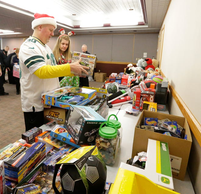 Steve and Carmen Klein pick out a gift for a child Friday, Dec. 21, 2018 at the Fond du Lac Police Department, to be added to a meal that will be delivered to one of 70 families as part of the Fond du Lac Police Department's Adopt a Family program.