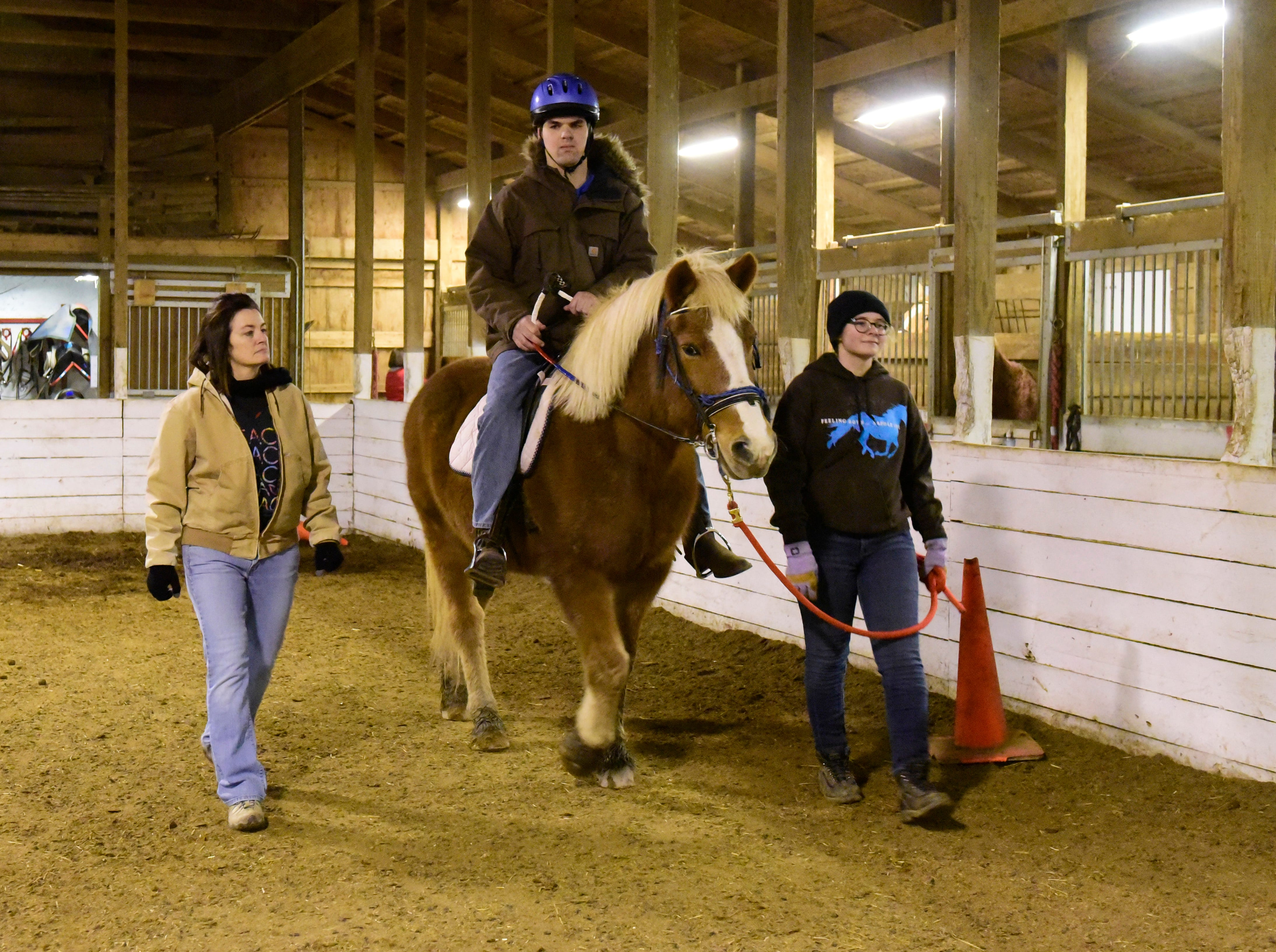 T.J. Stricker, 28, of Helena, middle, rides with the help of volunteers Trisha Tallman, left, and Ava Van Ness, right. He has cerebral palsy and is nonverbal.