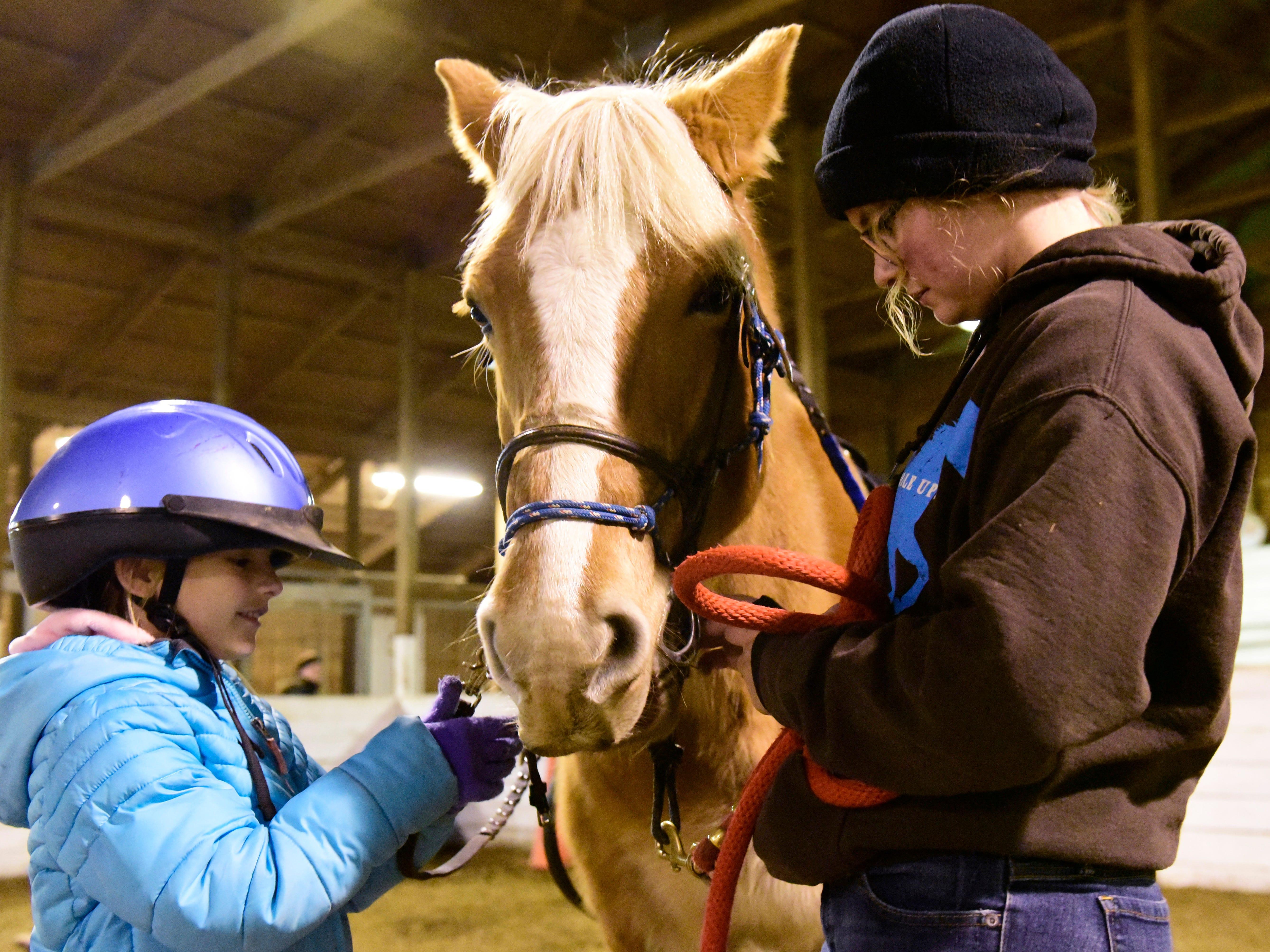 Aubrey Messa, 8, of Oak Harbor cares for her lesson horse, Gracie, a 13 year old Haflinger mare, with help from volunteer leader Ava Van Ness.
