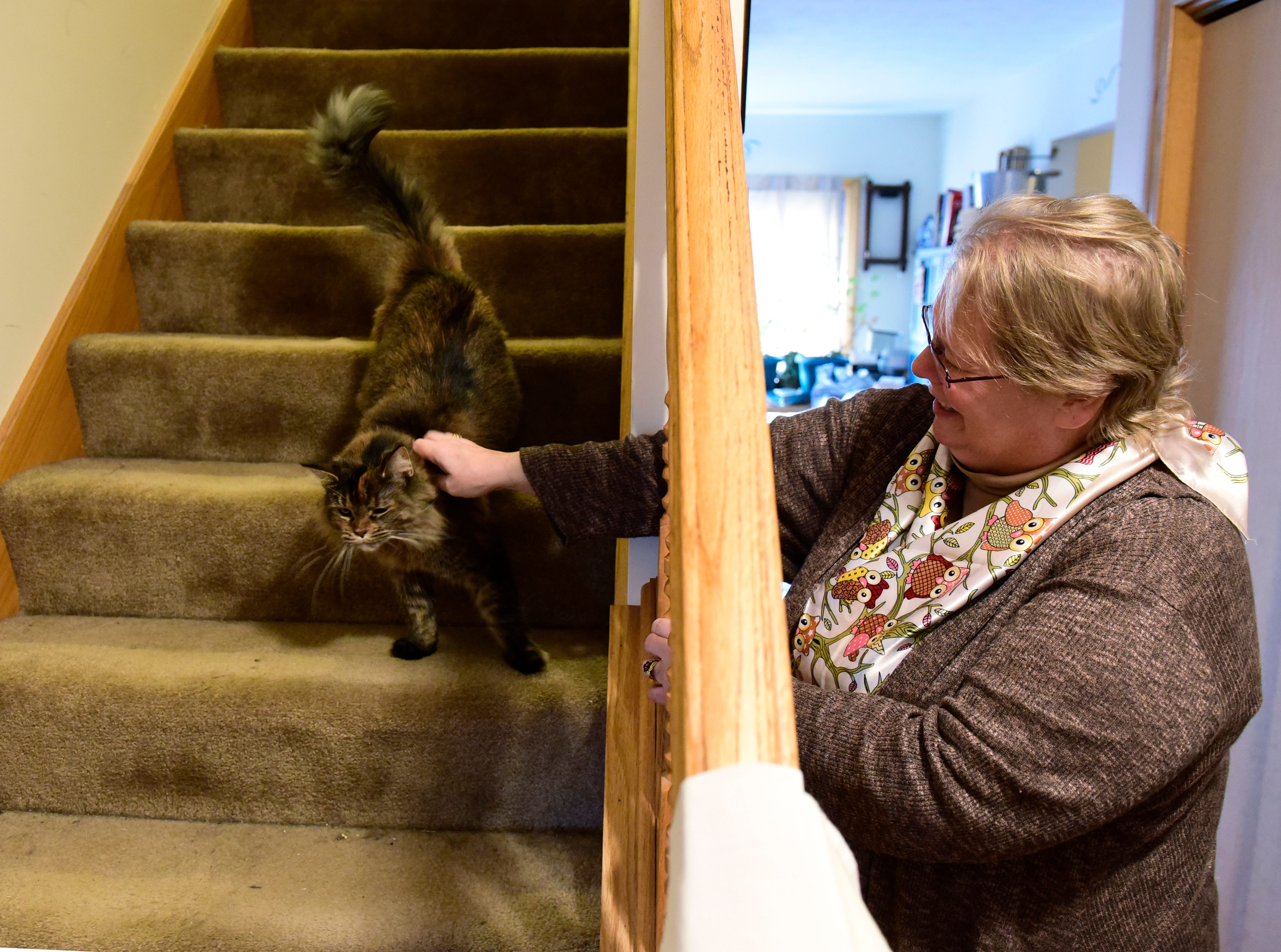 Rebekah Recker plays with her cat in her home. She said first came double vision in the middle of September, then her sight became blurred. Her balance started to fail and she has trouble walking around her home.