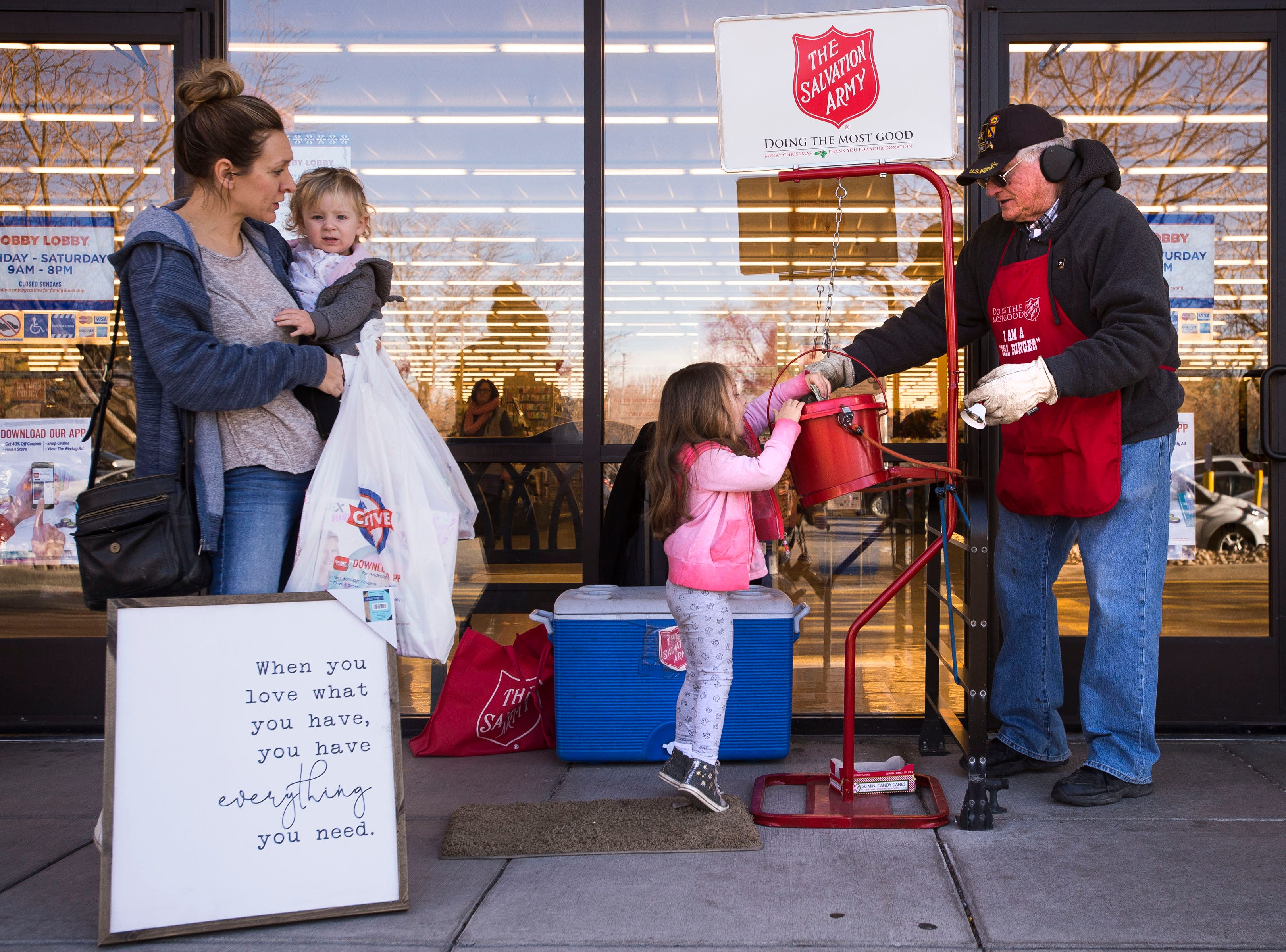 Salvation Army bell ringer Robert Thompson tips the bucket down a bit for 3-year-old Emerson Fry as Fry's mother, Taylor, and 1-year-old sister Georgia stand by on Friday, Dec. 21, 2018, in front of the Hobby Lobby on South College Avenue in Fort Collins, Colo.