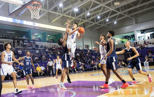 IMG Academy's Josh Green drives to the basket over University High School's Scottie Barnes during the fifth place semi-final game of the City of Palms Classic at Suncoast Credit Union on Friday.  IMG blew out University 88-51.