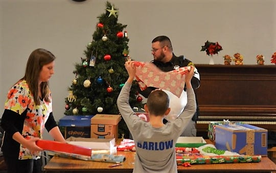 Deputy Joe LeBreck of the Oconto County Sheriff's Office, his girlfriend Ali Neumeier, a nurse at the jail wrap gifts with a youth during Shop With a  Cop on Dec. 8 at Oconto City Hall.