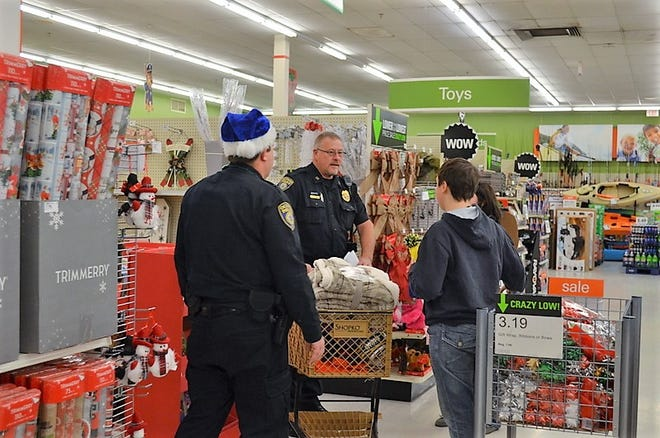 Oconto Police Capt. Randy Van Hulle talks with youths while they Shop with a Cop on December 2018 at Shopko Hometown in Oconto. At left is officer Mike Damit. Shopko has for years been a partner in the Shop with a Cop program.
