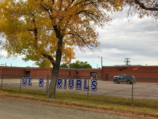 """A sign woven into the fence at Geraldine High School reads: """"We R Rivals."""""""
