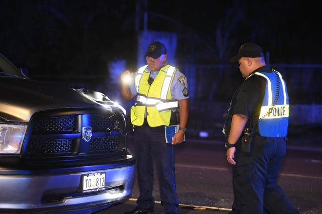 Investigators assess damage to a vehicle after a pedestrian was hit on Route 10 in Mangilao near American Medical Clinic Friday night