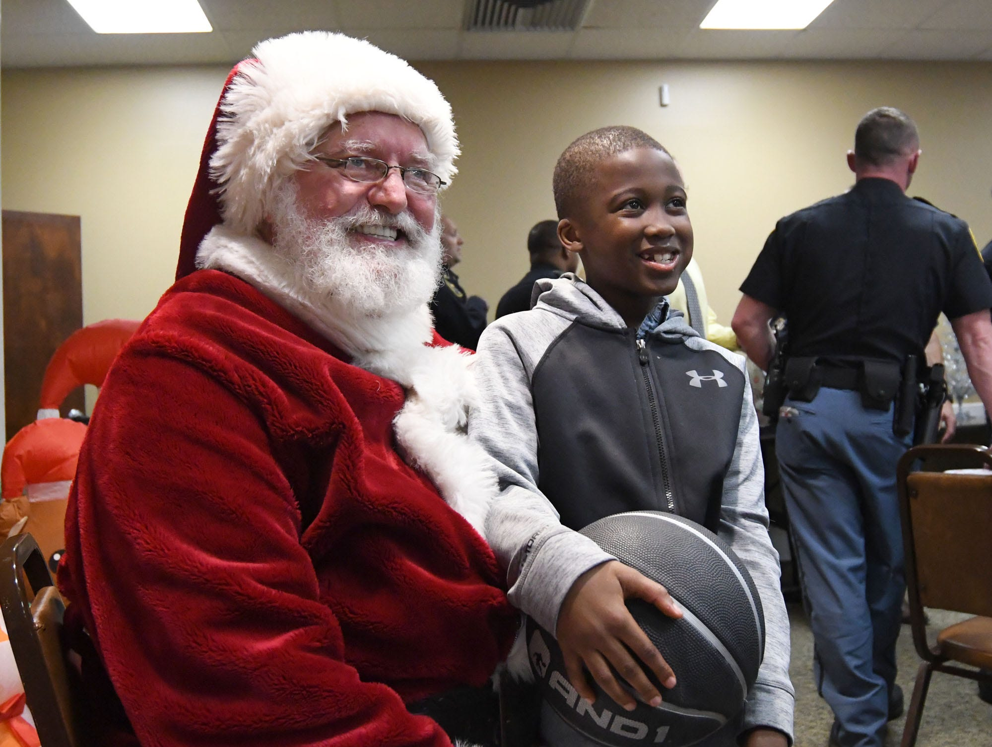 Devin Thompson, 8, gets presents from Santa Claus during the Hattiesburg Police Department's Victim Service Unit's Hearts of Hope Christmas party for victims affected by violent crimes at Jackie Sherrill Community Center on Thursday, December 20, 2018.