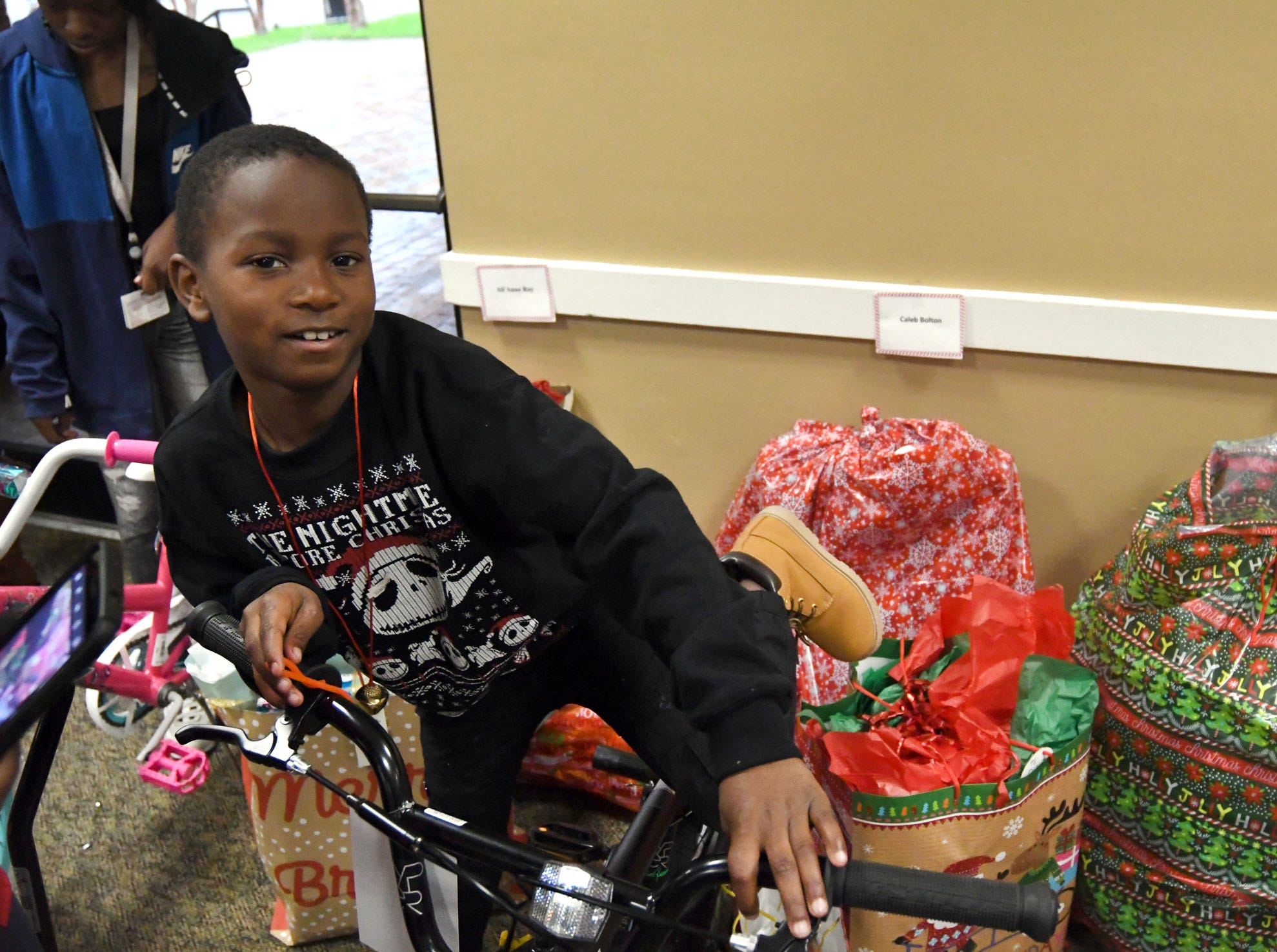 Caleb Bolton gets on his new bike during the Hattiesburg Police Department's Victim Service Unit's Hearts of Hope Christmas party for victims affected by violent crimes at Jackie Sherrill Community Center on Thursday, December 20, 2018.