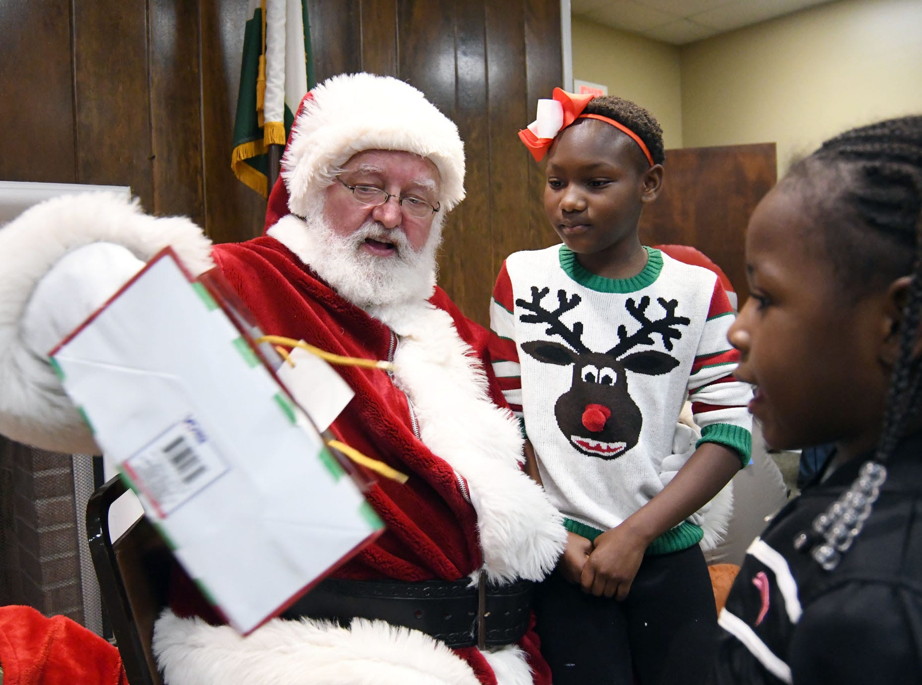 Santa Claus gives out presents during the Hattiesburg Police Department's Victim Service Unit's Hearts of Hope Christmas party for victims affected by violent crimes at Jackie Sherrill Community Center on Thursday, December 20, 2018.