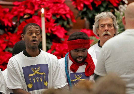 Members of the Matthew's Voices: Side by Side Community Choir sing during the National Homeless Persons' Memorial Service at Roberts Park United Methodist Church, Friday, Dec. 21, 2018.