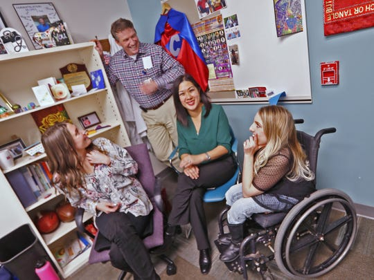 Dr. Chuck Dietzen, center standing, laughs with Julie-Anne Bignal, Amy Duarte, and Kaycee Marshall at Riley Hospital for Children, Thursday, Dec. 20, 2018.  The group are among those who have developed superhero outfits for Riley kids.