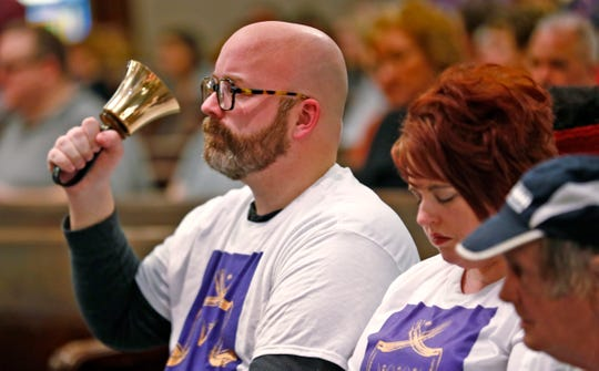 Jason Fishburn, the director of Matthew's Voices: Side by Side Community Choir, rings a bell for each name called of homeless people who died in 2018, during the National Homeless Persons' Memorial Service at Roberts Park United Methodist Church, Friday, Dec. 21, 2018.