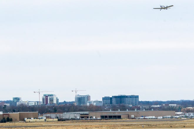 An airplane takes off while the Hilton Garden Inn, Chauncey and the Hyatt Place and Rise at Riverfront Landing buildings are seen in the background on Friday, Dec. 21, 2018, from Grace Drive near the Iowa City Municipal Airport.