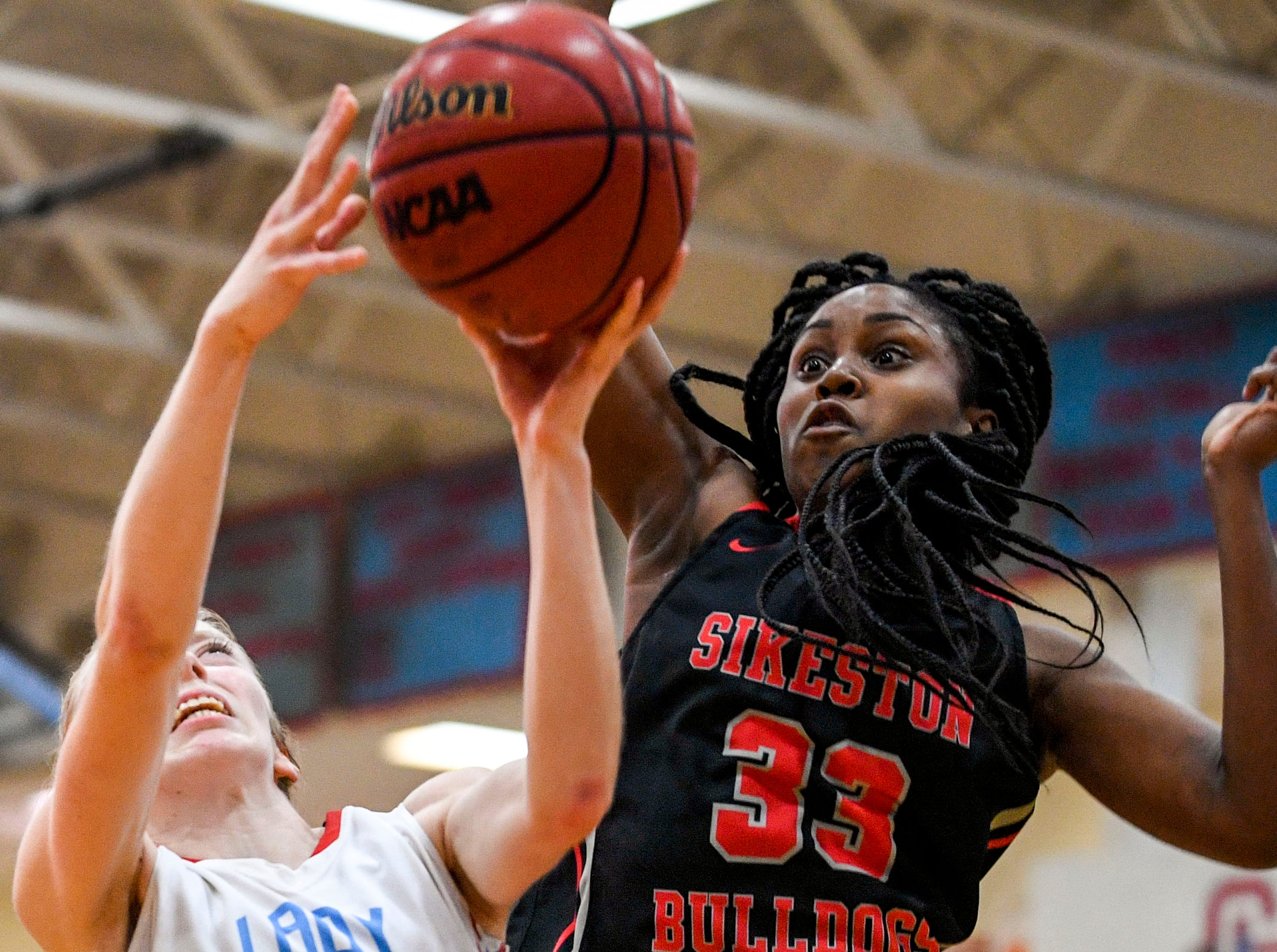 Sikeston's Karris Allen (33) jumps to try and block a shot from Gibson County's KJ White (32) in a TSSAA girls basketball game between Gibson County and Sikeston (MO) in the Gibson County Christmas Tournament at Gibson County High School in Dyer, Tenn., on Thursday, Dec. 20, 2018.