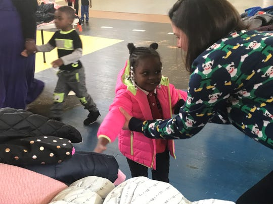Washington-Douglas Assistant Director Elizabeth Bryant helps a girl try on her new coat.