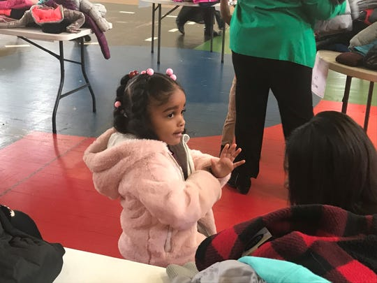 One girl checks the sleeves on the coat she picked out at the coat drive at Washington-Douglass on Thursday.