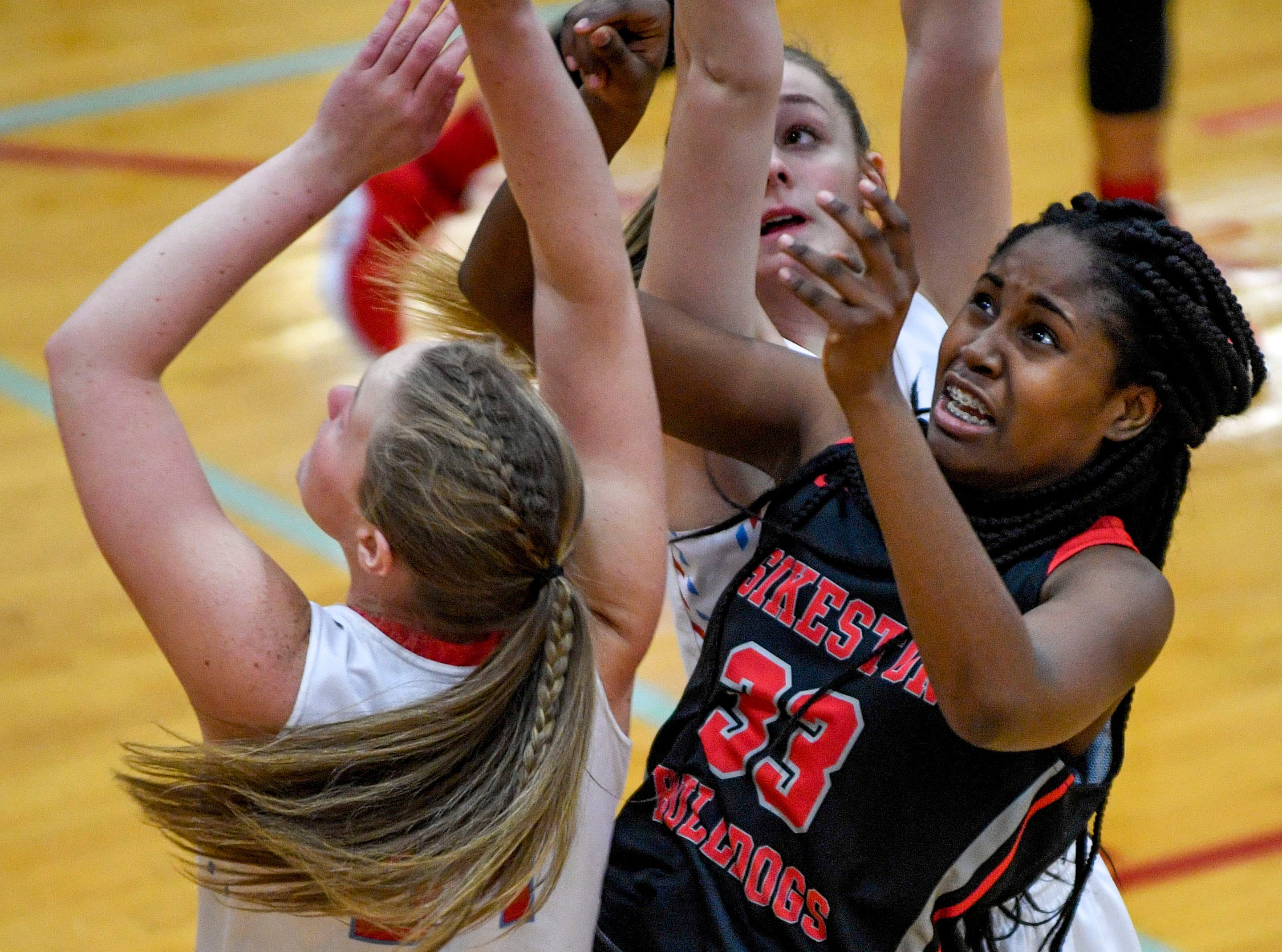 Sikeston's Karris Allen (33) takes a jump shot amongst a cluster of Gibson County players in a TSSAA girls basketball game between Gibson County and Sikeston (MO) in the Gibson County Christmas Tournament at Gibson County High School in Dyer, Tenn., on Thursday, Dec. 20, 2018.